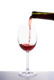 Rött vin som häller in i vinexponeringsglas Arkivfoto