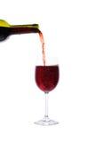 Rött vin som häller in i wineexponeringsglas Arkivbilder
