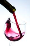Rött vin som häller in i wineexponeringsglas Arkivfoto