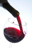Rött vin som häller in i wineexponeringsglas Royaltyfri Bild