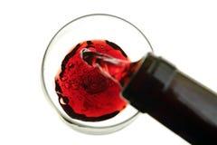 Rött vin som hälls in i ett exponeringsglas som isoleras på vit Royaltyfri Foto