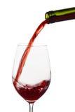 Rött vin som hälls in i ett vinexponeringsglas Fotografering för Bildbyråer
