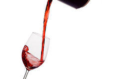 Rött vin som hälls in i ett vinexponeringsglas Royaltyfri Bild