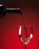 Rött vin som hälls in i vinexponeringsglas Arkivbilder