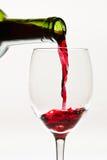 Rött vin som ner häller till exponeringsglaset Arkivfoto
