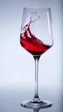 Rött vin som plaskar i det eleganta exponeringsglaset. Royaltyfria Foton