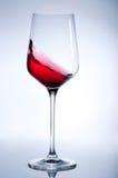 Rött vin som plaskar i det eleganta exponeringsglaset på grå färg Arkivbilder