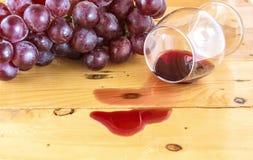 Rött vin som spills på stilleben för tabellöverkant Royaltyfri Foto