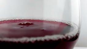 Rött vindroppe som ner faller in i drinkexponeringsglas på vit bakgrund, näringsjukvårdbegrepp som skjuter med den snabba kameran arkivfilmer