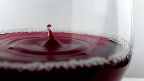 Rött vindroppe som ner faller in i drinkexponeringsglas på vit bakgrund, näringsjukvårdbegrepp som skjuter med den snabba kameran stock video