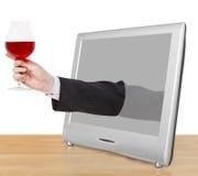 Rött vinexponeringsglas i den manliga handen lutar ut TVskärmen Arkivfoton