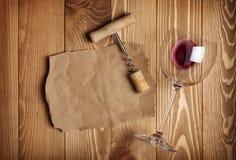 Rött vinexponeringsglas, korkskruv och papper för din anmärkning Fotografering för Bildbyråer