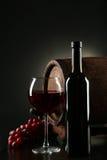 Rött vinexponeringsglas med flaskan och trumma på en svart bakgrund Arkivfoton