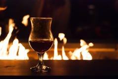 Rött vinexponeringsglas med hemtrevlig brand bak den Arkivbild