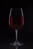 Rött vinexponeringsglas med vin på svart bakgrund Royaltyfria Bilder