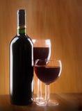Rött vinexponeringsglas och buteljerar på en träbakgrund Arkivbild