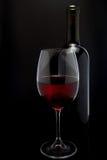 Rött vinexponeringsglas och en flaska i svart bakgrund Royaltyfria Foton