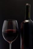 Rött vinexponeringsglas och en flaska i svart bakgrund Royaltyfri Foto