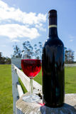 Rött vinexponeringsglas och flaska på en vitt trästolpe och stångstaket Royaltyfria Bilder