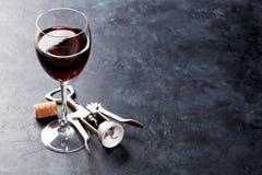 Rött vinexponeringsglas och korkskruv Fotografering för Bildbyråer