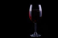 Rött vinexponeringsglas på den svarta bakgrunden Arkivbild