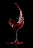 Rött vinexponeringsglas på svart bakgrund royaltyfri illustrationer