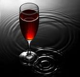 Rött vinexponeringsglas på vatten skvalpar bakgrund Royaltyfri Fotografi