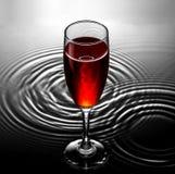 Rött vinexponeringsglas på vatten skvalpar bakgrund Arkivbild