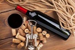 Rött vinflaska, exponeringsglas, korkar och korkskruv ovanför sikt Arkivfoton