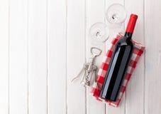 Rött vinflaska, exponeringsglas och korkskruv Royaltyfria Foton