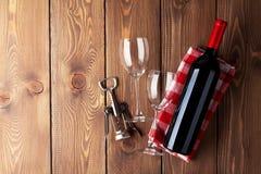Rött vinflaska, exponeringsglas och korkskruv på trätabellen Arkivbilder