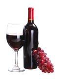 Rött vinflaska och exponeringsglas av vin med nya druvor Fotografering för Bildbyråer