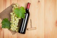 Rött vinflaska och grupp av vita druvor Arkivfoton