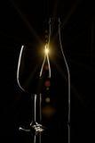 Rött vinflaska och vinexponeringsglas på svart bakgrund Royaltyfri Bild