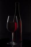 Rött vinflaska och vinexponeringsglas på svart bakgrund Fotografering för Bildbyråer