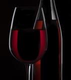 Rött vinflaska och vinexponeringsglas på svart bakgrund Arkivfoton