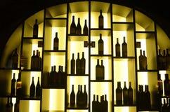Rött vinflaskor, tända hyllor, affär Royaltyfria Bilder