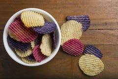Rött, vit och blått färgade potatischiper i en bunke Arkivfoto