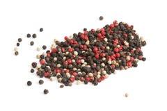 Rött, vit och svartpeppar på vit. Arkivbild