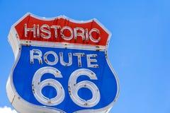 Rött, vitt och blått Route 66 tecken som är främst av blå himmel royaltyfri bild