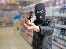 Röveri i lager Rånaren är sikta, och hota med vapnet shoppa in Arkivfoto