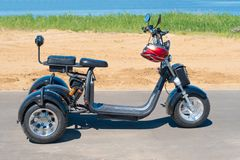 Rússia, Bolgar - 8 de junho de 2019 Kol Gali Resort Spa: Motocicleta elétrica de três rodas na praia Caminhada em um 'trotinette' foto de stock