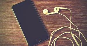 Rússia, Chelyabinsk, o 7 de janeiro de 2015 iPhone preto novo 6 de Apple e fones de ouvido na tabela Foto de Stock