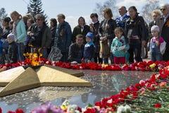 RÚSSIA, Chita - 9 de maio: Colocar floresce no fogo eterno na celebração do dia da vitória no WWII imagem de stock royalty free