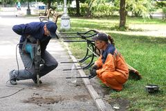 Rússia, cidade de Magnitogorsk, - agosto, 19, 2015 Os trabalhadores ajustaram o banco no parque da cidade fotografia de stock royalty free