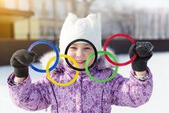 Rússia, cidade de Yasny, região de Orenburg, pista de gelo da escola, 12-10 Anéis olímpicos nas mãos de uma menina bonita foto de stock