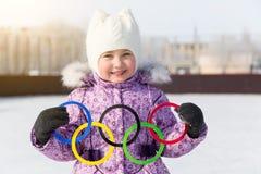 Rússia, cidade de Yasny, região de Orenburg, pista de gelo da escola, 12-10 Anéis olímpicos nas mãos de uma menina bonita imagens de stock royalty free