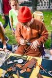 R?ssia, cidade Moscou - 6 de setembro de 2014: Mestre, curtume do trabalhador Um homem novo faz um produto do couro Nas m?os de fotos de stock