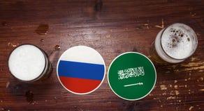 Rússia contra Pousas-copos de Arábia Saudita na barra com pintas da cerveja foto de stock