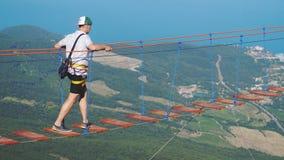 Rússia, Crimeia, o 3 de julho de 2017 Equipe o passeio na corda na ponte de suspensão longa sobre o abismo Fotografia de Stock